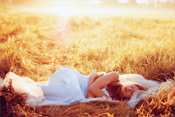 hình ảnh cô gái nằm giữa đồng cỏ và ánh nắng bình minh