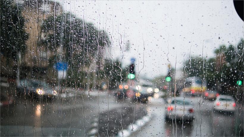 Blurred street scene through car windows with rain drop