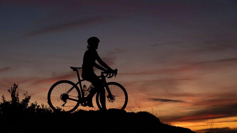 ảnh chụp bóng người đạp xe trên đỉnh núi khi hoàng hôn buông xuống