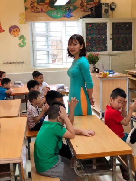 hình ảnh cô giáo và học sinh đang đi kiểm tra bài