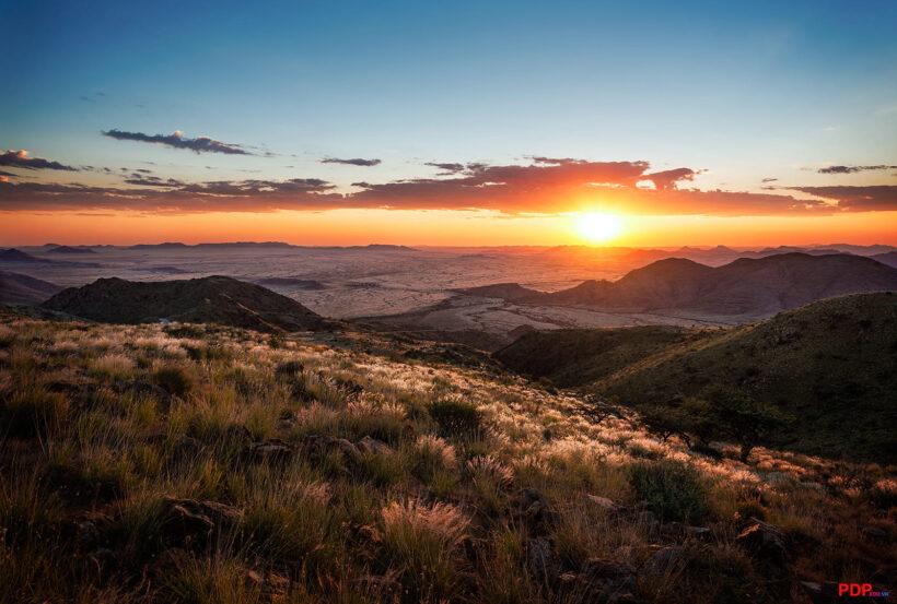 hình ảnh hoàng hôn buồn trên đồng cỏ và núi