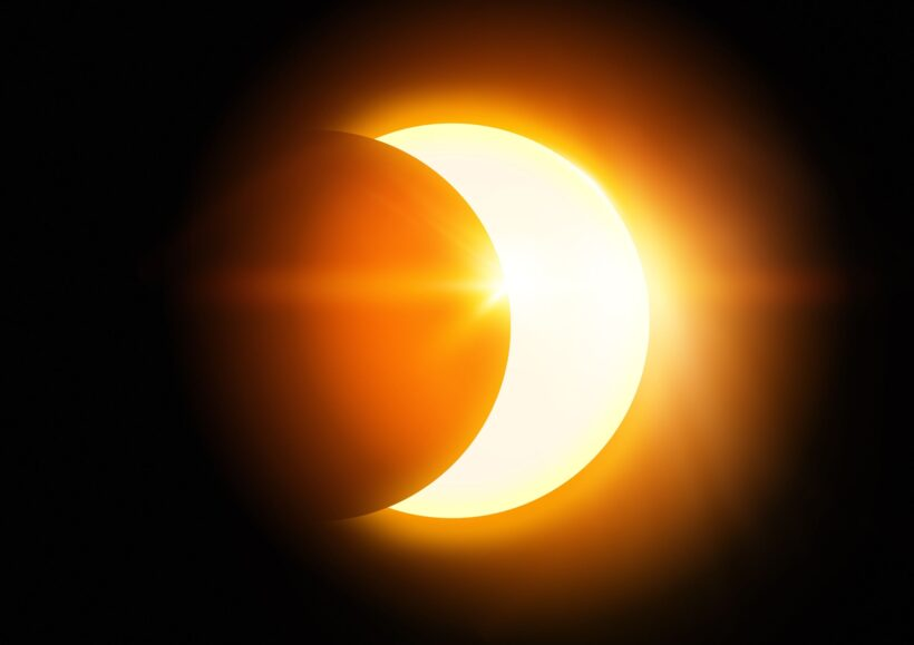 21816275 - the moon covering the sun in a partial eclipse.